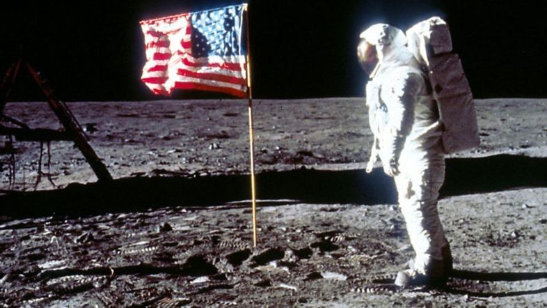 _107563830_buzz-aldrin-poses-next-to-flag